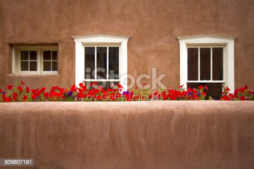 Santa Fe style: red flowers behind adobe wall. Shot in Santa Fe, New Mexico. Copy space on wall.