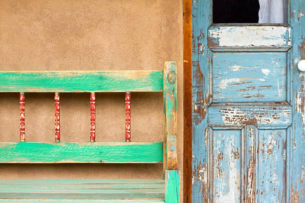 santa-fe-stil: rustikale veranda, old blue door, adobe wall - mexikanische möbel stock-fotos und bilder