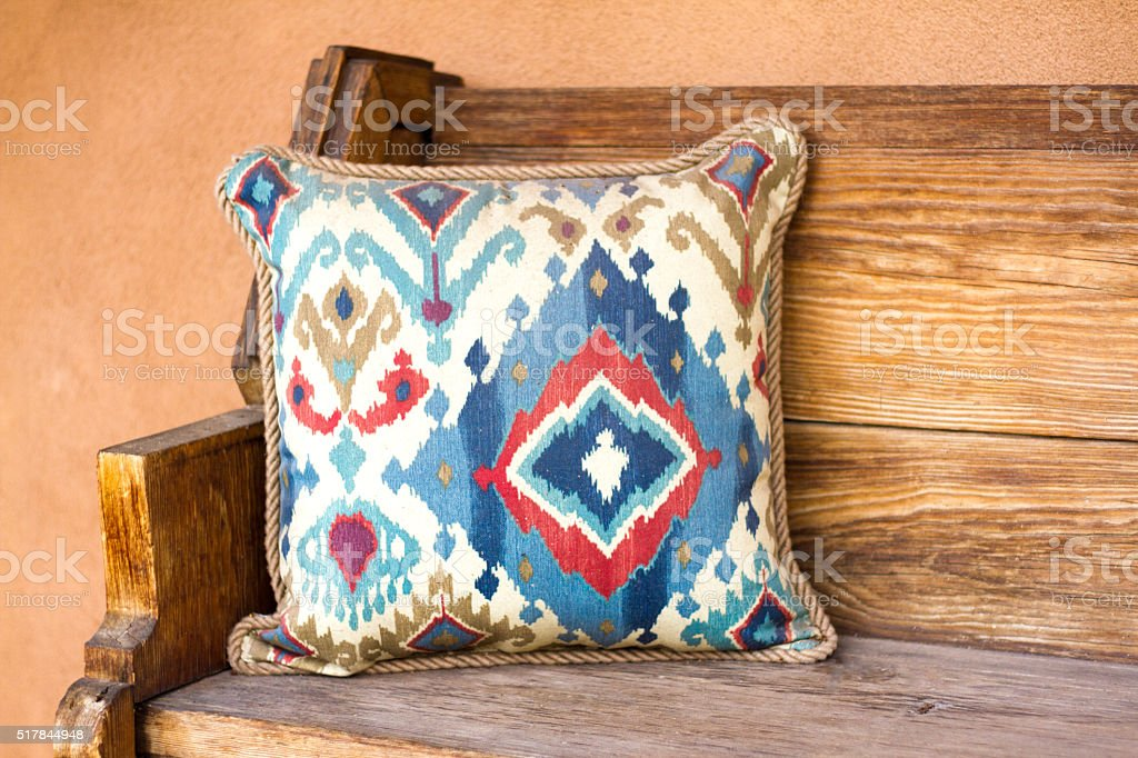 Santa Fe Style: Rustic Wood Bench, Southwest Pillow, Adobe Wall stock photo