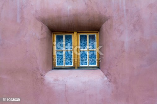 Santa Fe Style: tiny bullnose window with white lace curtains set into thick pinkish adobe walls. Shot in Santa Fe, NM. Copy space on walls.