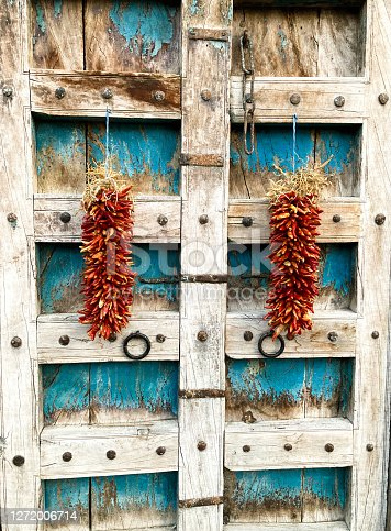 Santa Fe Style: Two Red Ristras on Antique Wood Doors. Shot in Santa Fe, NM.