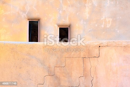Santa Fe style: two windows behind a cracked adobe wall. Copy space available.