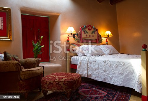 Santa Fe/Southwest style: colorful rustic-chic bedroom with viga beams, adobe walls that are hand-troweled with a