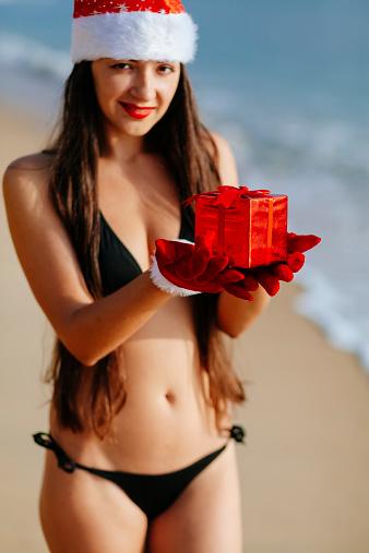 1155046257 istock photo santa girl in bikini hanging christmas gift in hands 527860499