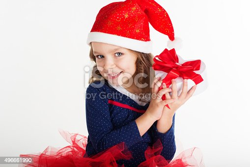 1061876006istockphoto Santa girl is holding gift box with red ribbon 496661990