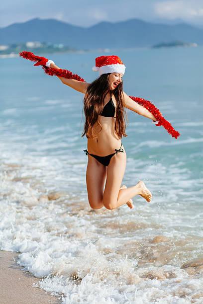 santa mädchen geht im meer am strand - weihnachten vietnam stock-fotos und bilder