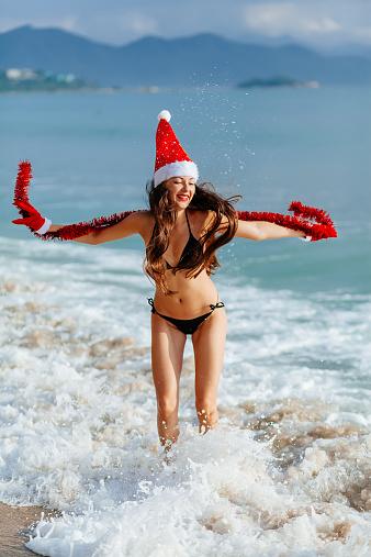 1155046257 istock photo santa girl jumping in the sea on the beach 528163243