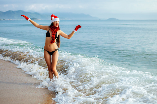 1155046257 istock photo santa girl making wish on the beach in tropics 529177361