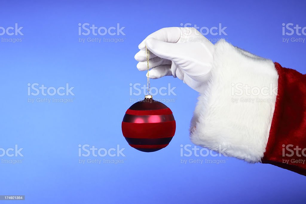 Santa Hands: Holding Red Ornament on Blue royalty-free stock photo