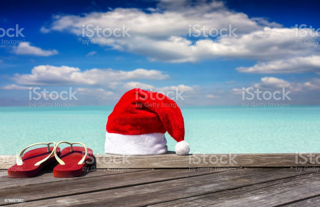 Santa hat and red flip flops on a pier in the tropics stock photo