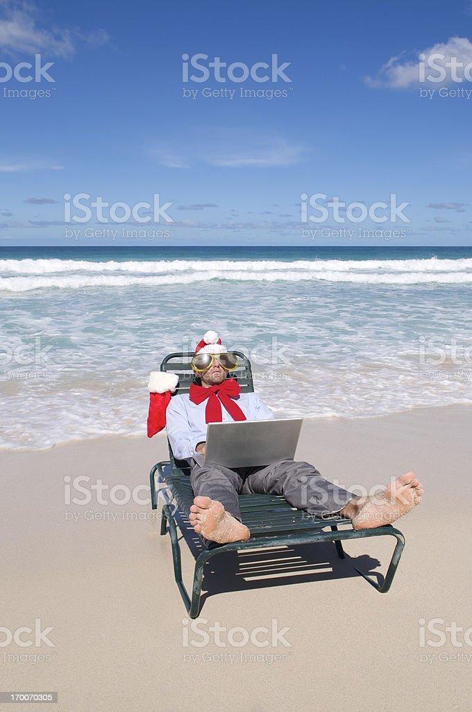 Santa Hat Businessman Relaxes on Beach Chair stock photo