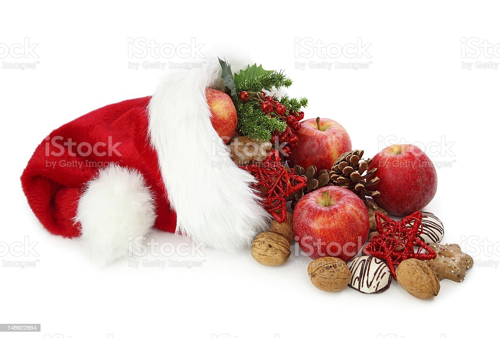A Santa hat filled with Christmas decorations and treats royalty-free stock photo