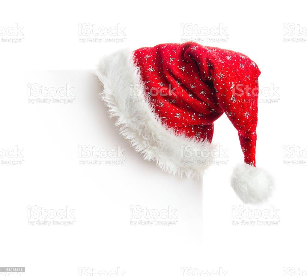 Santa hat hanging on white board stock photo
