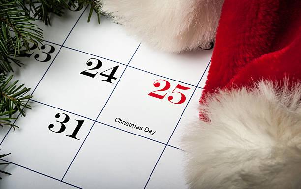 Santa hat laying on a Christmas calendar stock photo