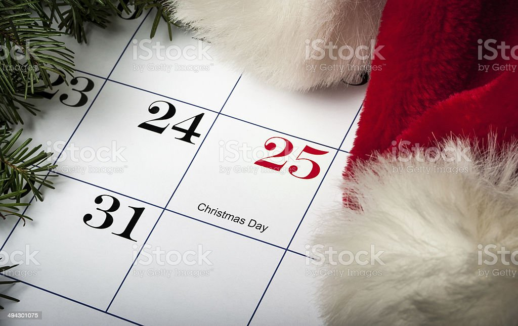 Santa hat laying on a Christmas calendar stock photo