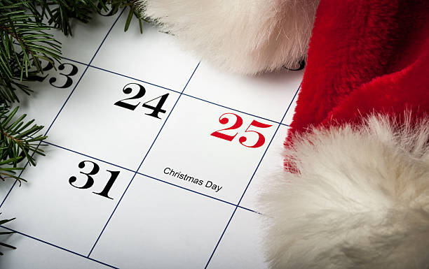Santa hat laying on a Christmas calendar Santa hat laying on a calendar next to December 25th Christmas with evergreens december stock pictures, royalty-free photos & images