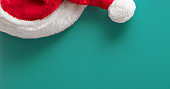 Red Santa hat on a teal background. Space for copy - you can add you message.