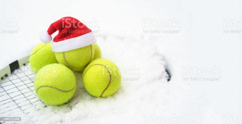 Santa hat on tennis ball, set of tennis balls on racket on white snow...