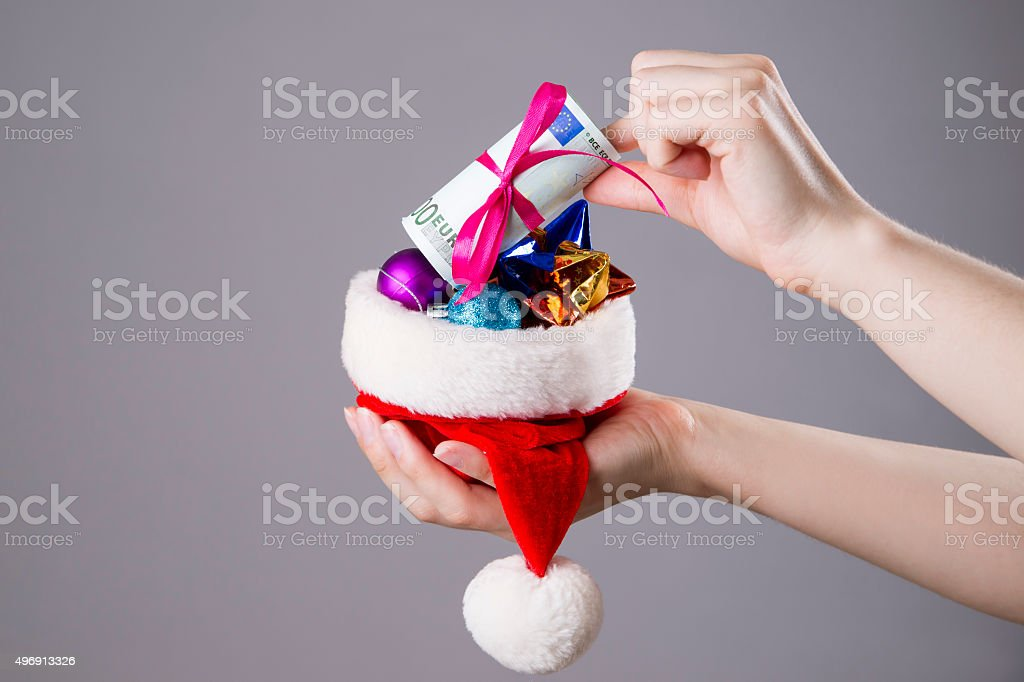 Santa hat with money in woman hands stock photo