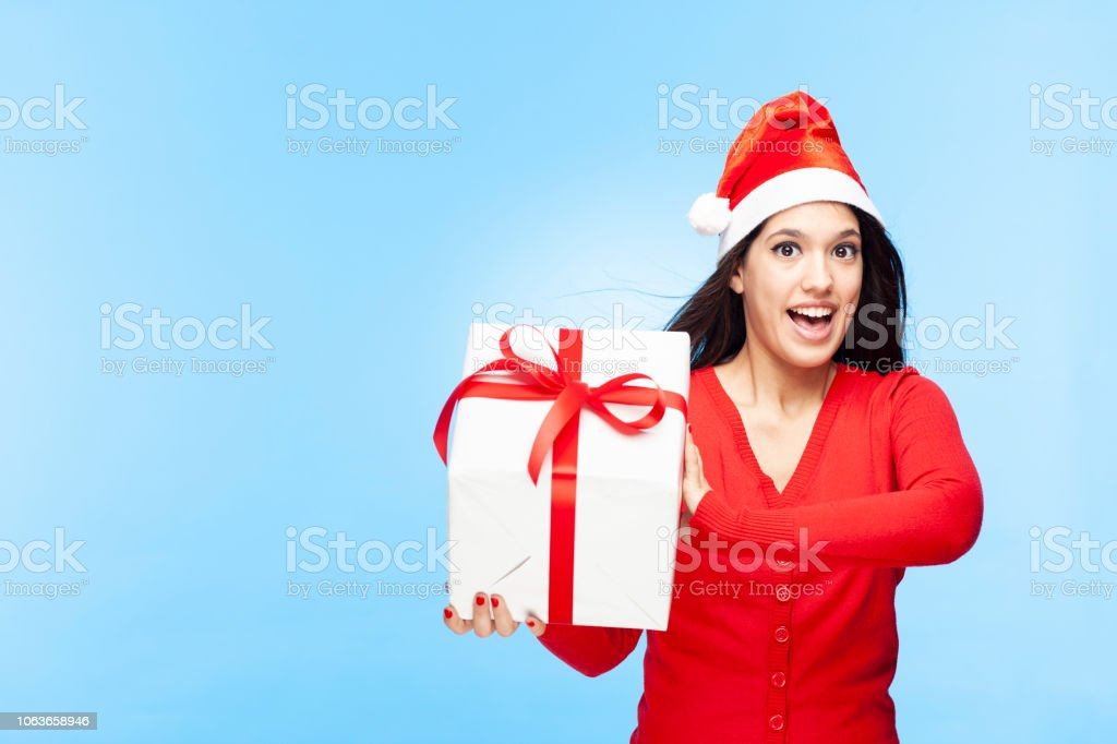 Portrait of a surprised woman in Santa hat holding gift box. The...