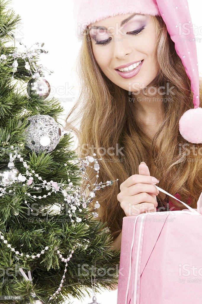 santa helper girl with gift box and christmas tree royalty-free stock photo