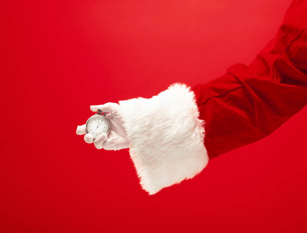 santa hält eine stoppuhr in der hand - weihnachtsprogramm stock-fotos und bilder