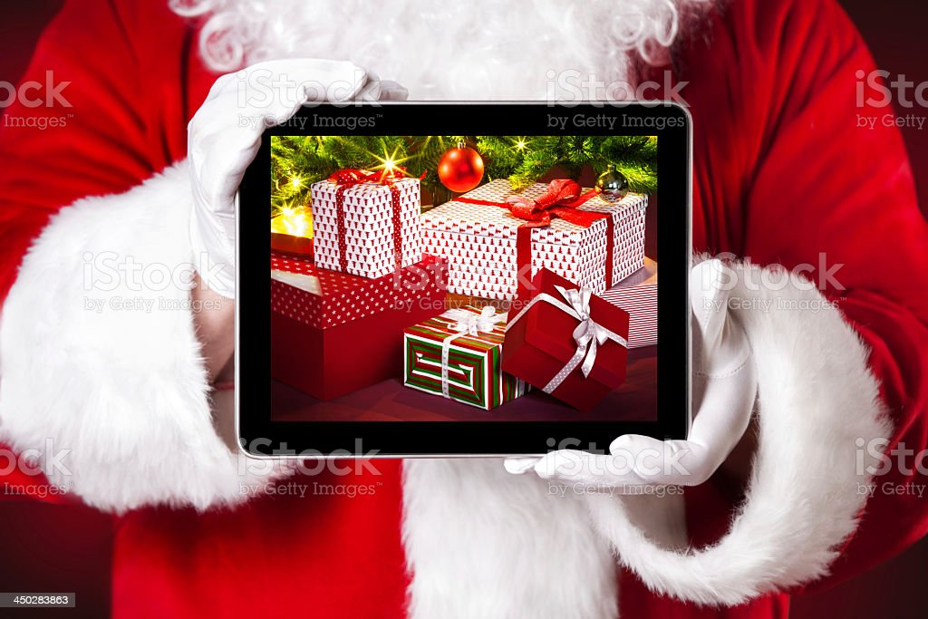 Santa holding a tablet which shows Christmas presents stock photo