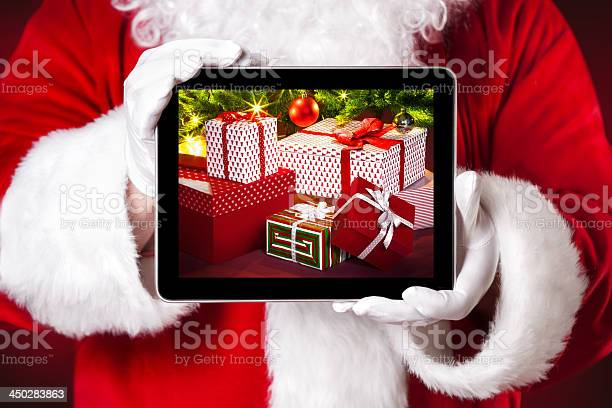 Santa Holding A Tablet Which Shows Christmas Presents Stock Photo - Download Image Now