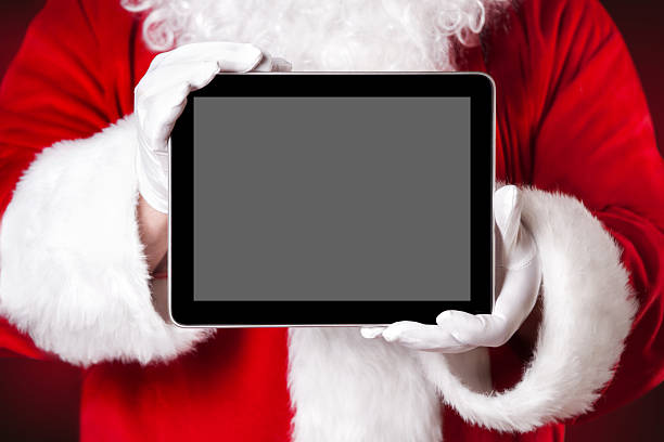 Santa holding a tablet with blank space stock photo