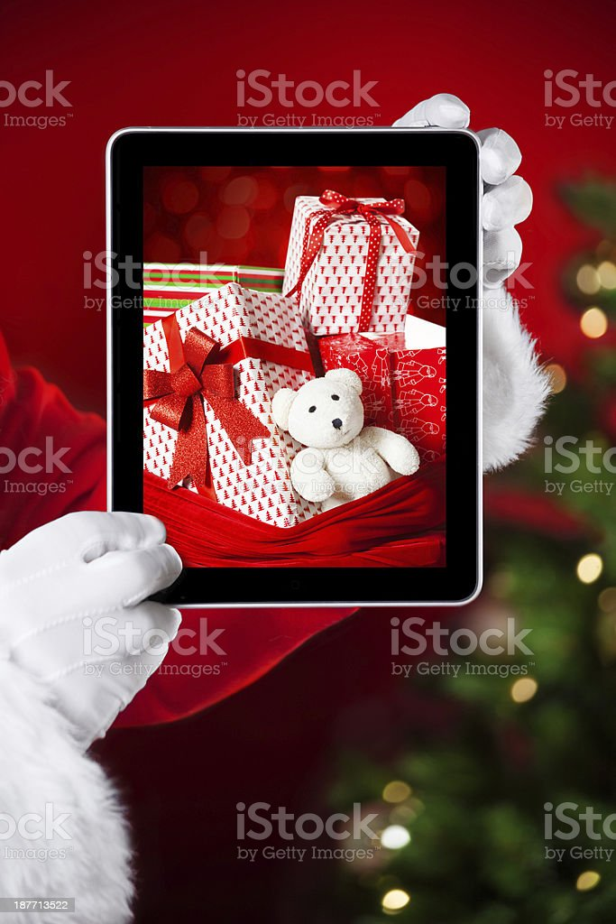 Santa holding a tablet with photo of christmas presents royalty-free stock photo