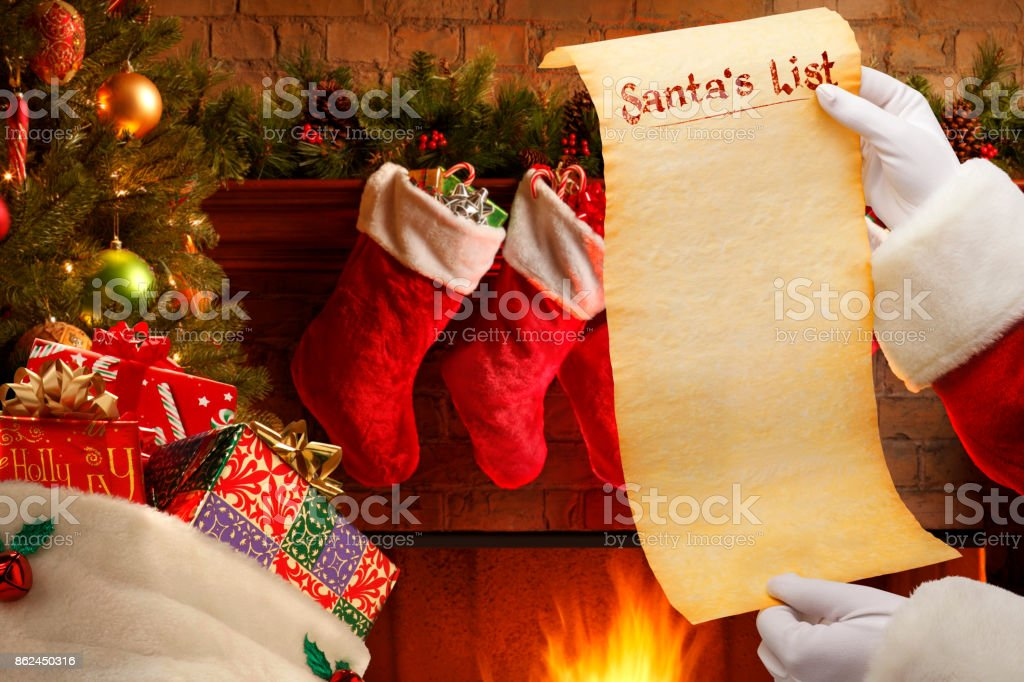 Santa Holding Blank List In Front Of Christmas Tree And Fireplace
