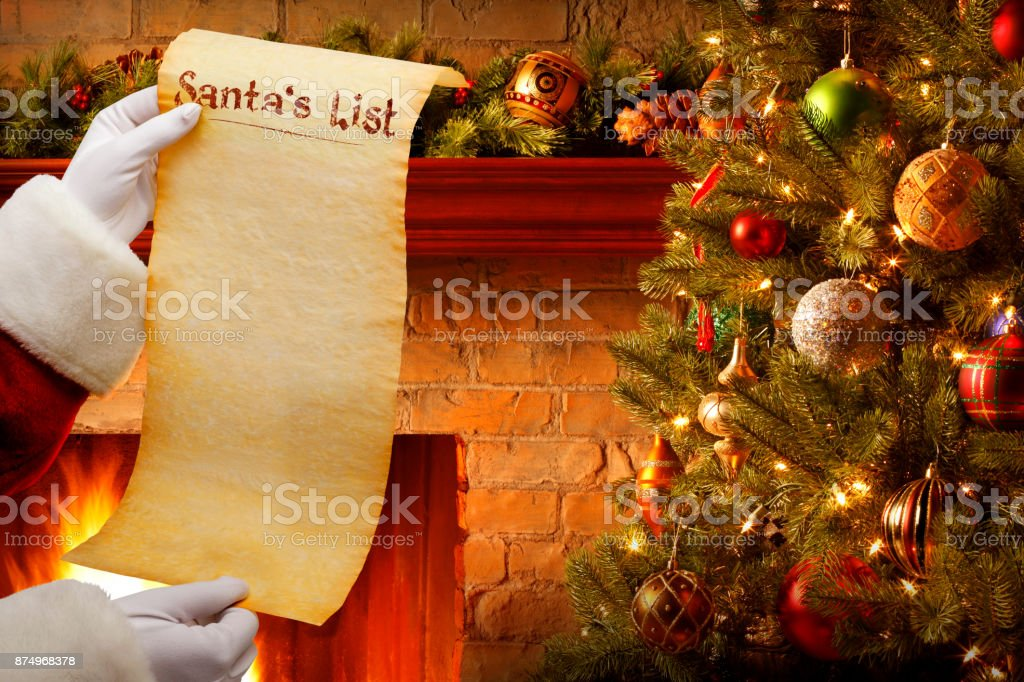 Santa Holding Blank List In Front Of Christmas Tree And Fireplace stock photo