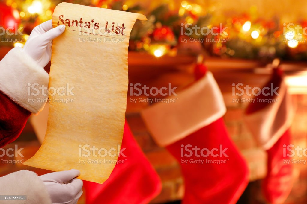 Santa Holding His List In Front Of Fireplace Mantelpiece stock photo