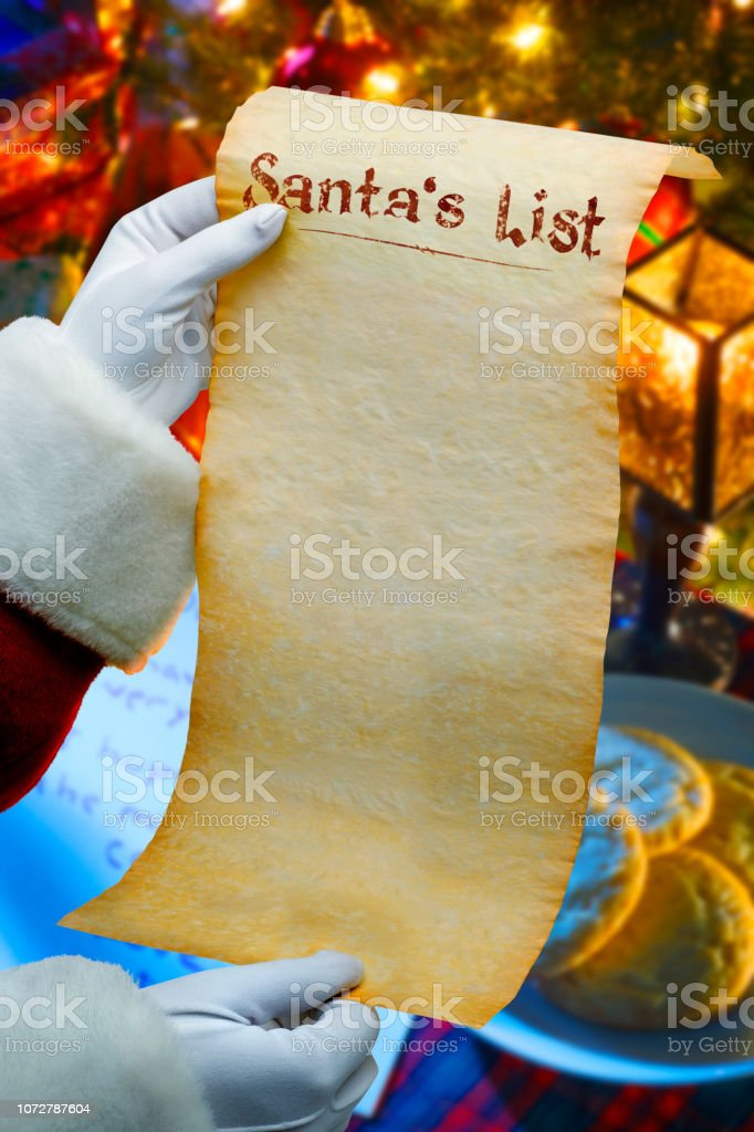 Santa Holding List In Front Of Cookies And Letter stock photo