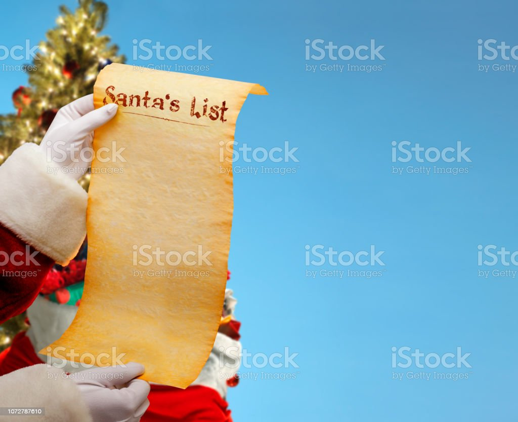 Santa Holds His Christmas List In Front Of Christmas Tree And Blue Background stock photo