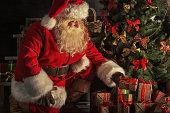 サンタがあるギフトボックスクリスマスツリーの下