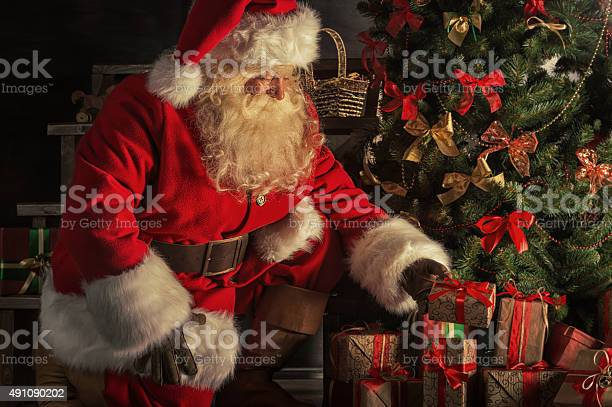 Santa is placing gift boxes under christmas tree picture id491090202?b=1&k=6&m=491090202&s=612x612&h=ybsw06ncfejrmxcynvepqz5vfgcmi fxqhyeplbjh4m=