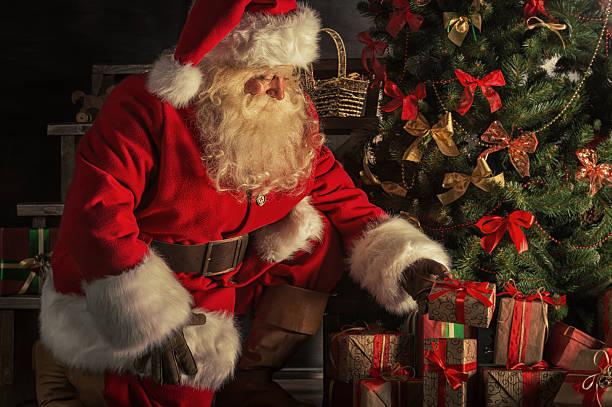 santa aufgibt geschenk-boxen unter dem weihnachtsbaum - santa stock-fotos und bilder