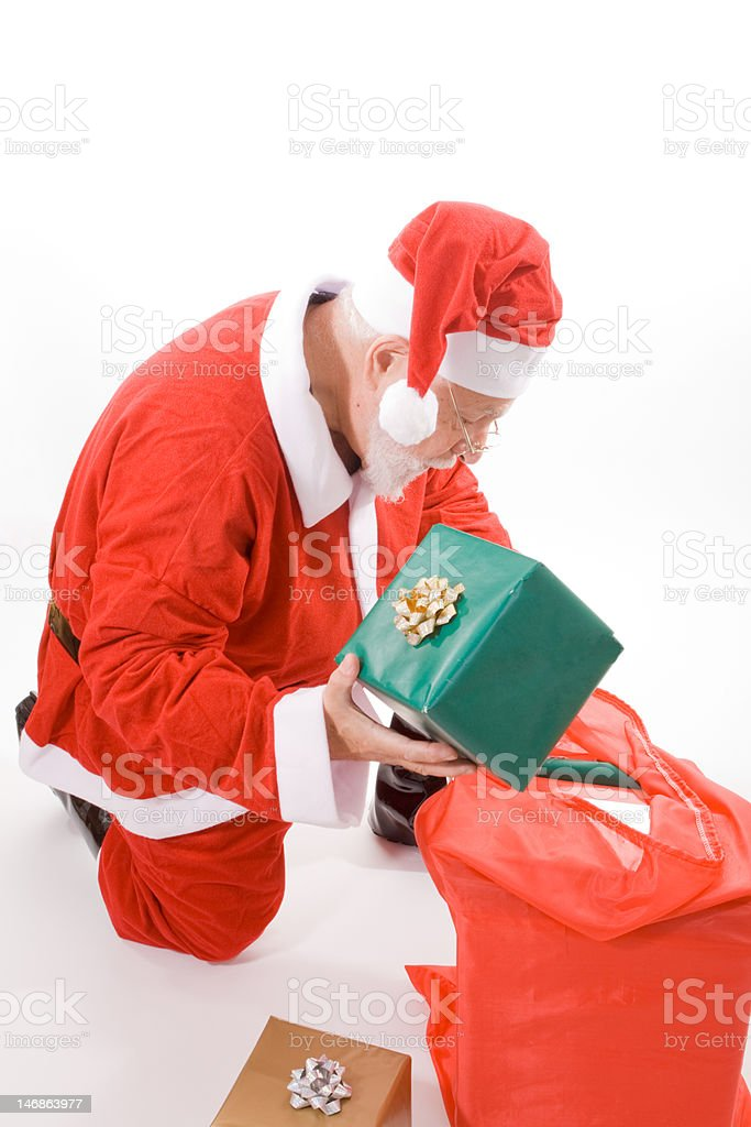 Santa Looking in Sack, Holding Present Gift Box, Isolated Background royalty-free stock photo