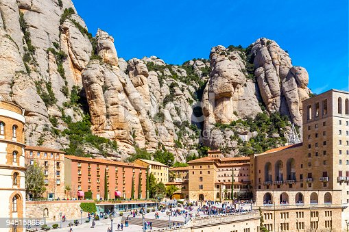 Top view of Santa Maria de Montserrat Abbey in Monistrol de Montserrat (Montserrat Monastery) and big, high rocky mountains  on sunny day, Catalonia, Spain