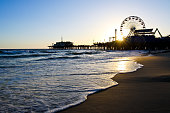 Los Angeles CA USA - May 27, 2019 : Taken this picture at sunset of the famous Santa Monica pier and the beach beside it. In the picture are the joy rides where tourists are enjoying the sunset.