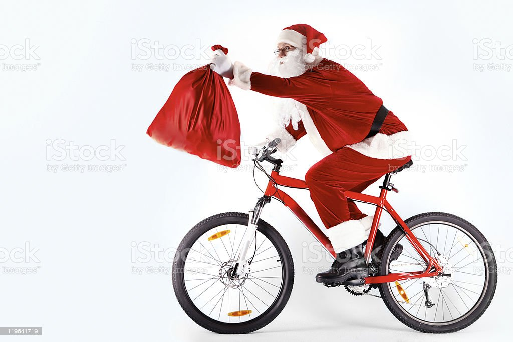 Santa on a bicycle holding out a sack royalty-free stock photo