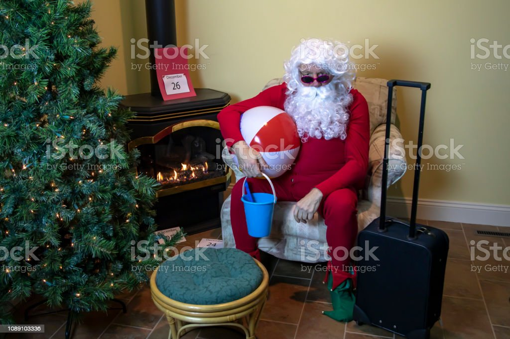 Santa Claus in house packed with beach toys for holiday wearing red...