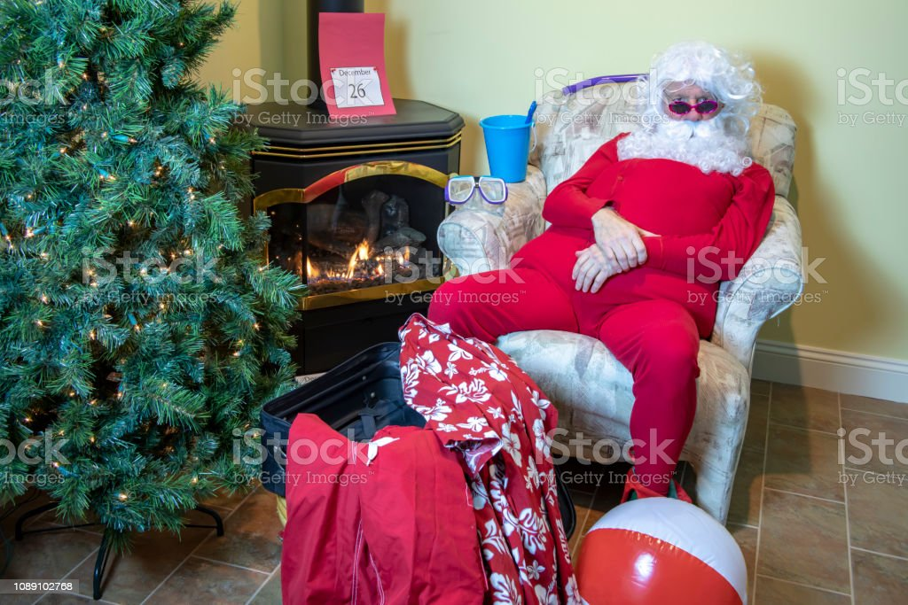 Santa Claus in house packing swim trunks and Hawaiian shirt with...