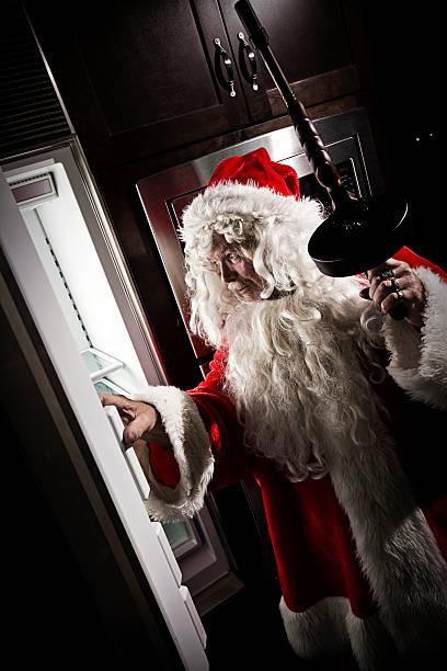 santa ispezionando frigorifero - santa claus tiptoeing foto e immagini stock