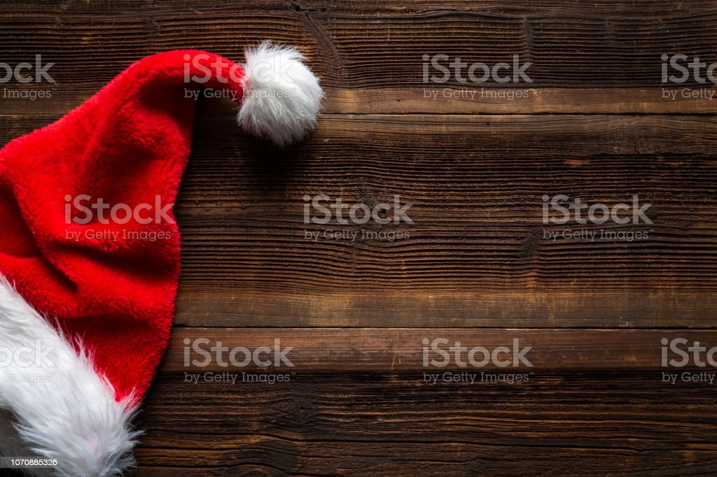 Santa red hat on wooden background, holiday Christmas concept Santa red hat on wooden background, holiday Christmas concept. Backgrounds Stock Photo