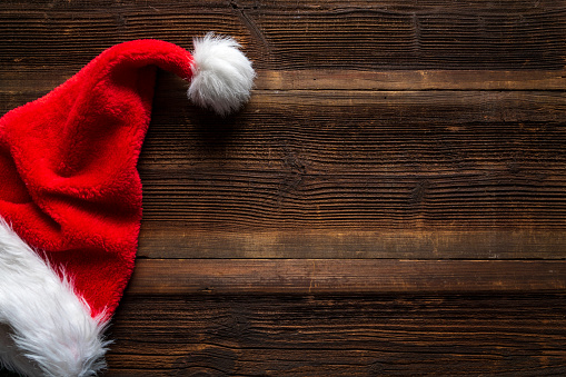 Santa Red Hat On Wooden Background Holiday Christmas Concept Stock Photo - Download Image Now