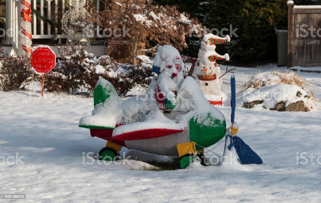 Santa sitzen auf einer Ebene, bedeckt in der Schnee-Dekoration – Foto