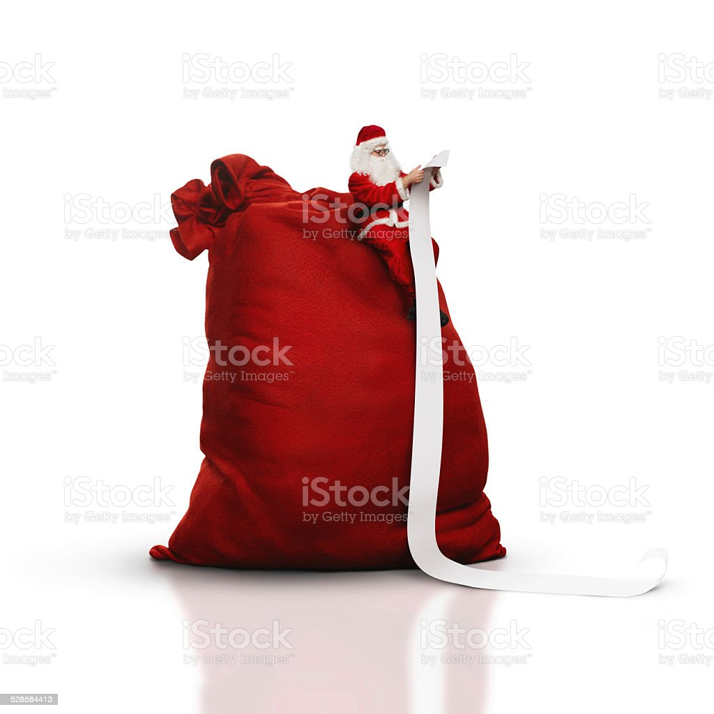 Santa sitting on big sack and reading long list stock photo
