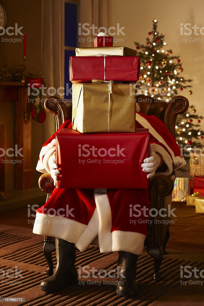 Santa sitting on chair with Christmas presents. royalty-free stock photo
